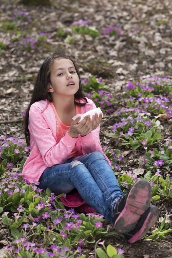Muchacha en la madera que estornuda debido a las flores imagen de archivo libre de regalías