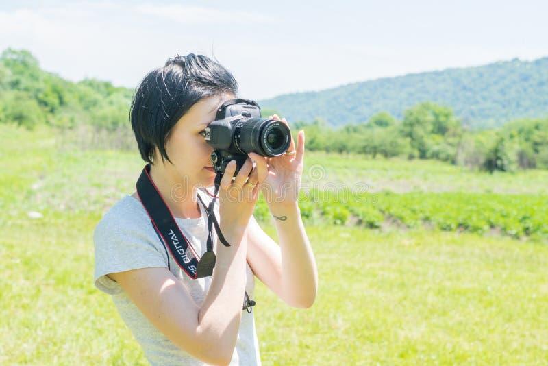 Muchacha en la naturaleza con una cámara imagen de archivo
