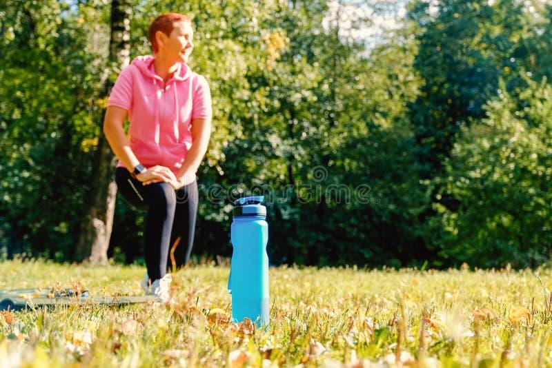 Muchacha en la naturaleza para los acontecimientos deportivos Se divierte la botella de agua Forma de vida sana foto de archivo