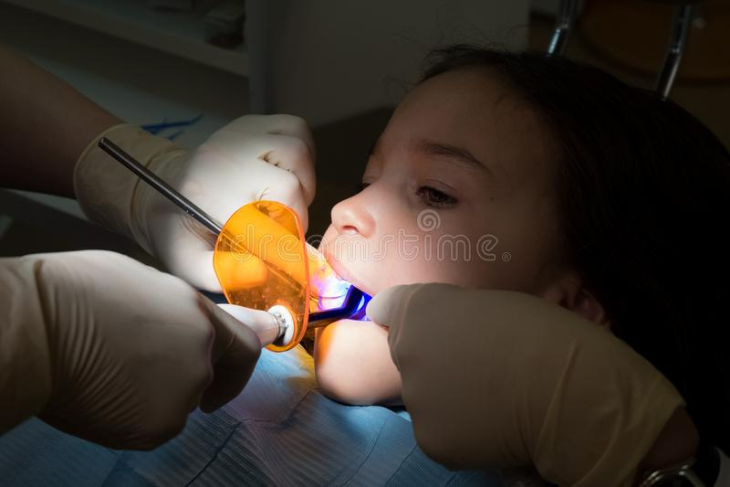 Muchacha en la oficina pediátrica de los dentistas, tratamiento de los dientes de bebé imagen de archivo