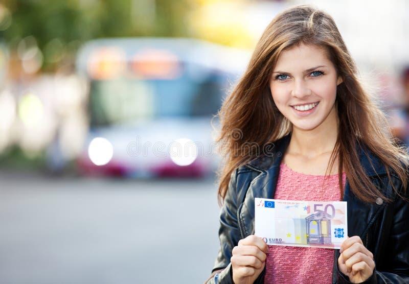 Muchacha en la parada de autobús que celebra el euro 50 foto de archivo
