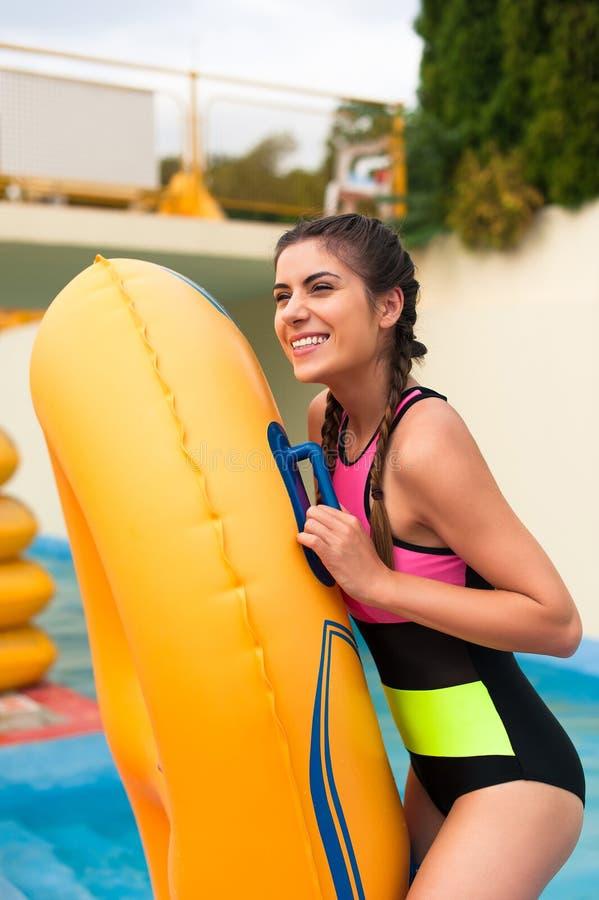 Muchacha en la piscina que tiene un buen rato, jugando con el flotador de goma fotografía de archivo