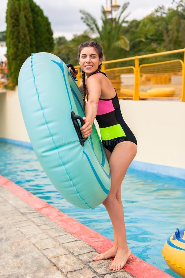 Muchacha en la piscina que tiene un buen rato, jugando con el flotador de goma fotografía de archivo libre de regalías