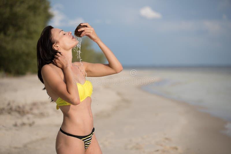 Muchacha en la playa con el coco imagenes de archivo