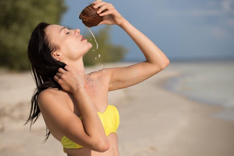 Muchacha en la playa con el coco imagen de archivo