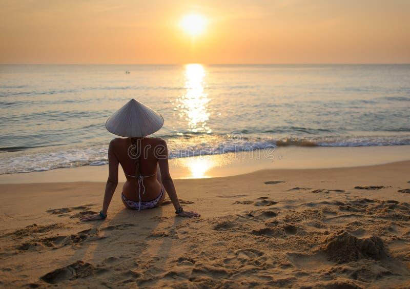 muchacha en la playa en la puesta del sol que lleva un sombrero 1 del arroz imagen de archivo libre de regalías