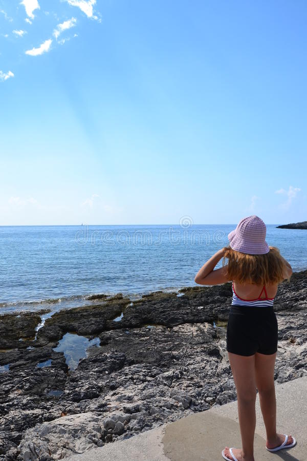 Muchacha en la playa rocosa foto de archivo