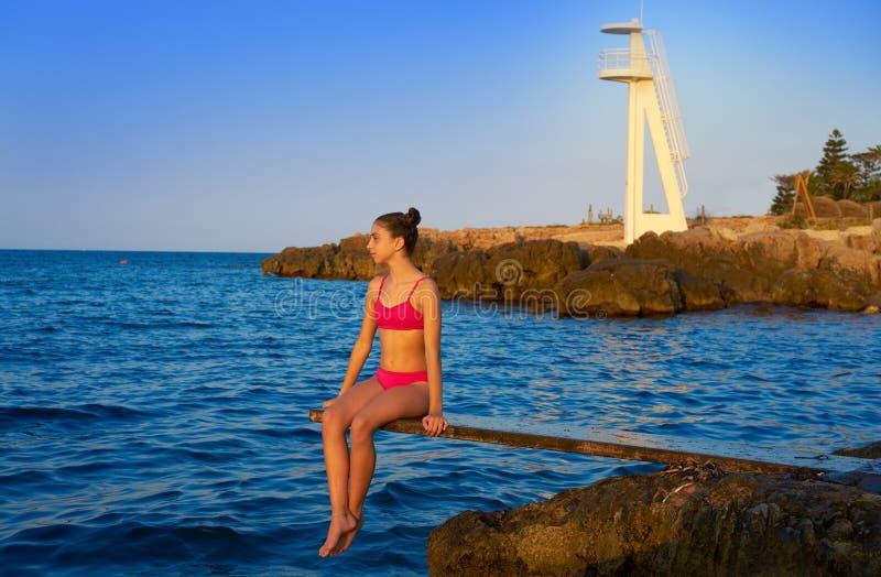 Muchacha en la puesta del sol de la playa en el trampolín imagen de archivo libre de regalías
