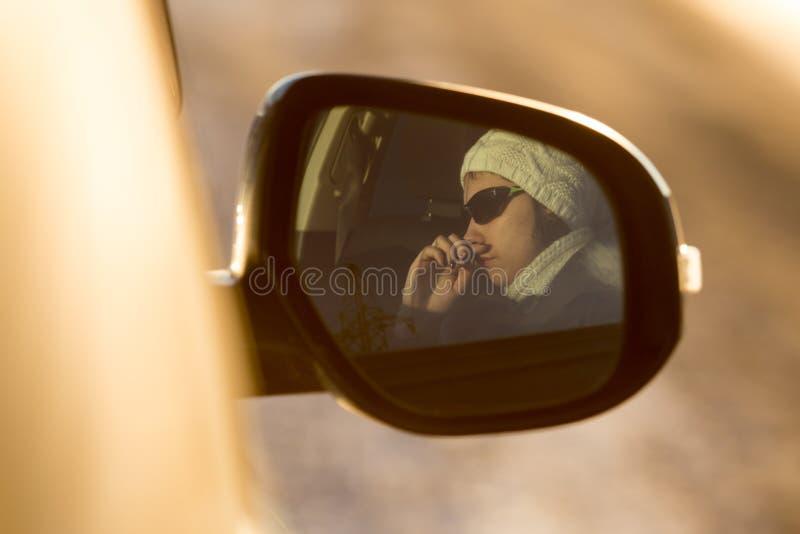 Muchacha en la reflexión de espejo en el auto en la puesta del sol imagen de archivo libre de regalías