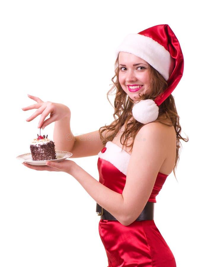 Muchacha en la ropa de Papá Noel con la torta sabrosa imagenes de archivo