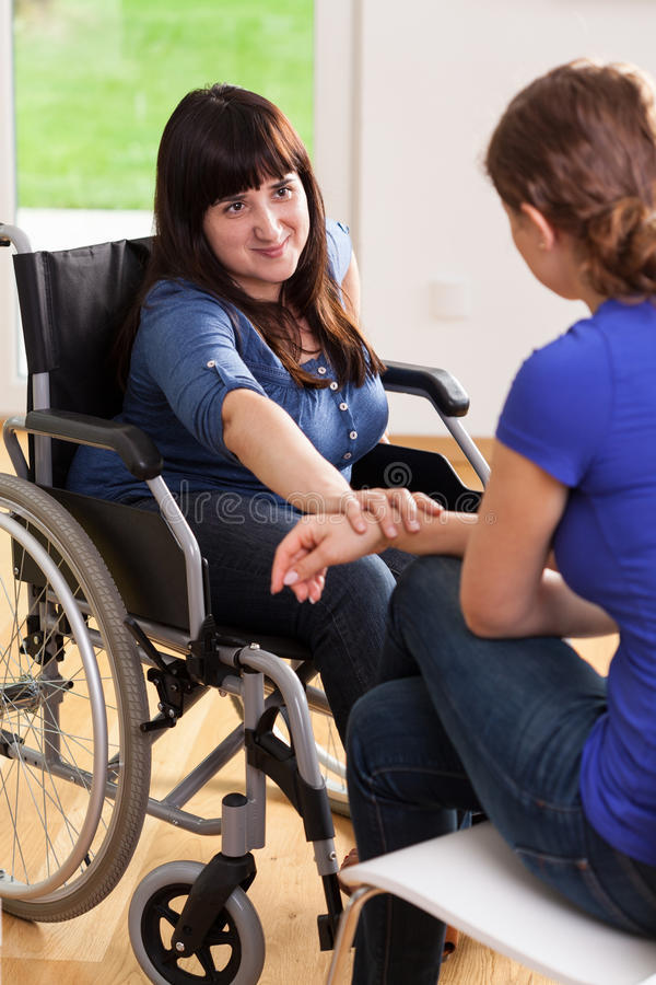 Muchacha en la silla de ruedas que habla con el amigo femenino imagen de archivo