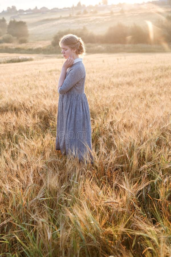 Muchacha en la situación azul del vestido en el amanecer en el campo de oídos en la luz de oro del sol colina y paisaje del país  foto de archivo libre de regalías