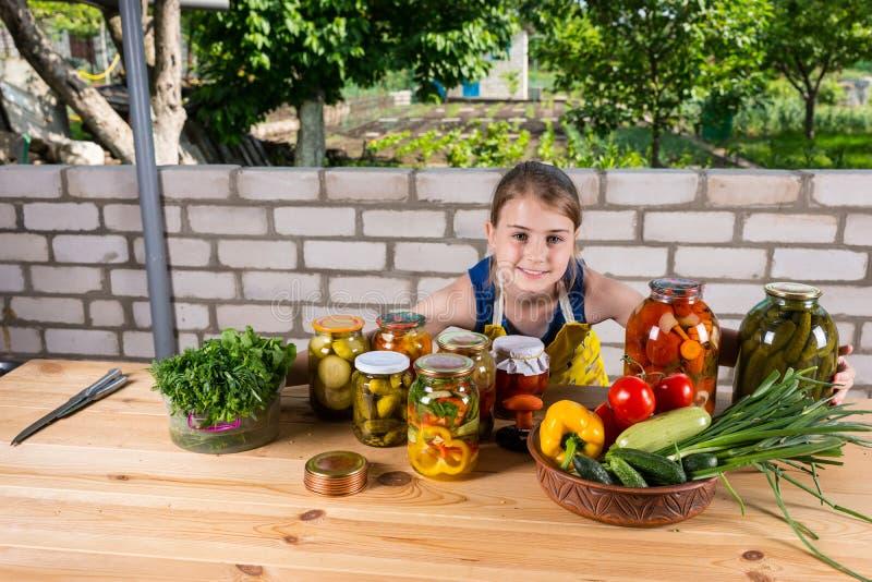 Muchacha en la tabla cubierta por las verduras y los cotos foto de archivo