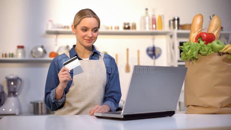 Muchacha en la tarjeta de banco de la tenencia de la cocina, satisfecha con la compra de la comida sobre Internet fotos de archivo