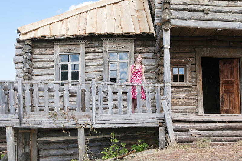 Muchacha en la terraza de una casa de madera vieja imagen de archivo