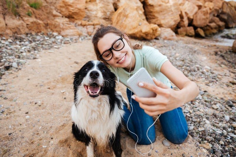 Muchacha en las lentes que toman el selfie con su perro en smartphone fotos de archivo