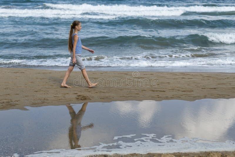Muchacha en las sonrisas rayadas de una camiseta, paseos a lo largo de la playa imagen de archivo
