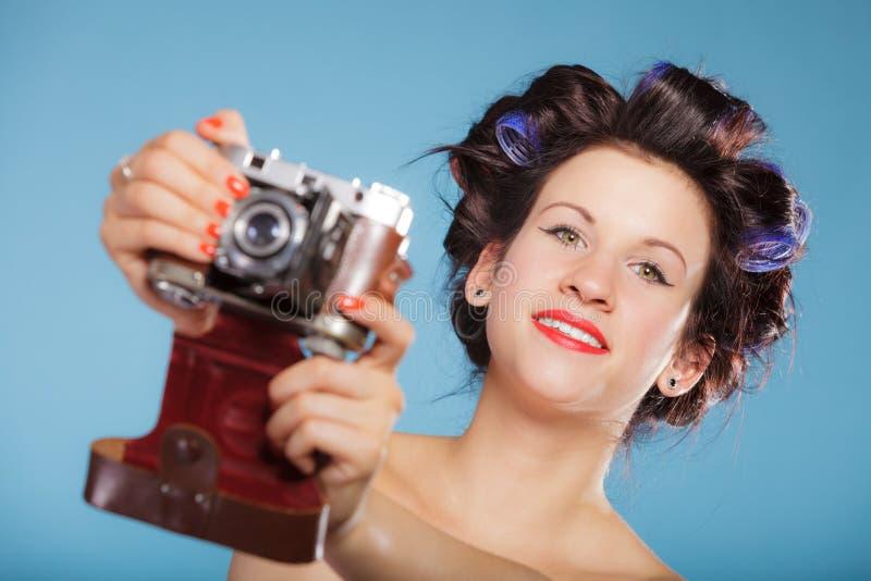 Muchacha en los bigudíes de pelo que toman la imagen con la cámara vieja fotos de archivo libres de regalías
