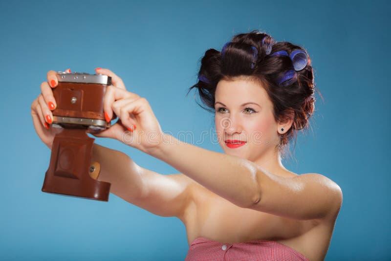 Muchacha en los bigudíes de pelo que toman la imagen con la cámara vieja imagen de archivo