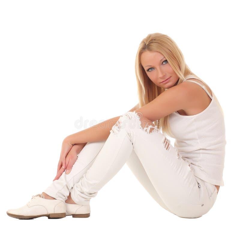 Muchacha en los pantalones blancos que se sientan en un fondo blanco foto de archivo