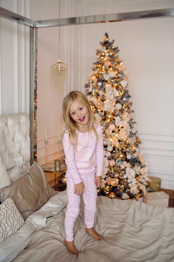 Muchacha en los pijamas rosados que se divierten en una cama grande el día de la Navidad fotografía de archivo