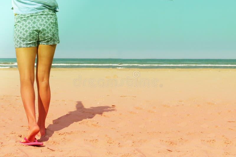 Muchacha en los wals de la playa hacia el mar imagenes de archivo