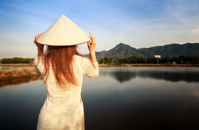 muchacha en parte trasera vietnamita del sombrero contra los lagos del país foto de archivo