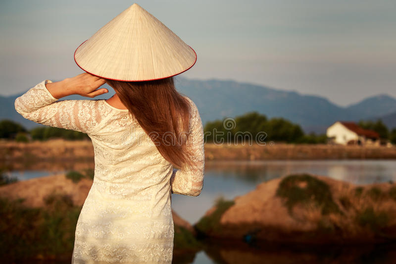 muchacha en parte trasera vietnamita del sombrero contra los lagos del país imágenes de archivo libres de regalías