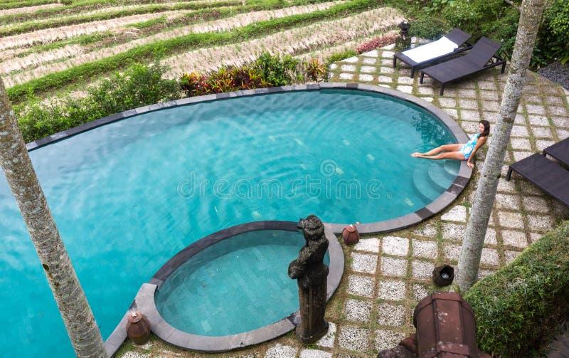 Muchacha en piscina del infinito hacia selva con palmtrees imagen de archivo libre de regalías