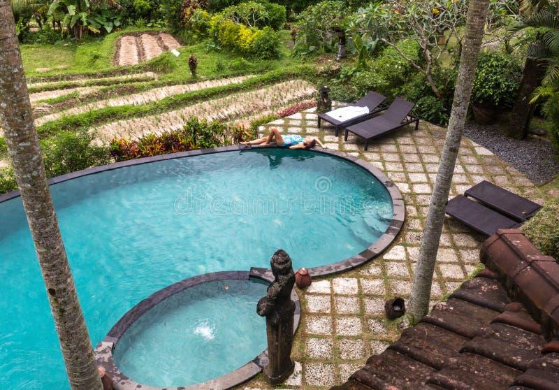 Muchacha en piscina del infinito hacia selva con palmtrees fotos de archivo