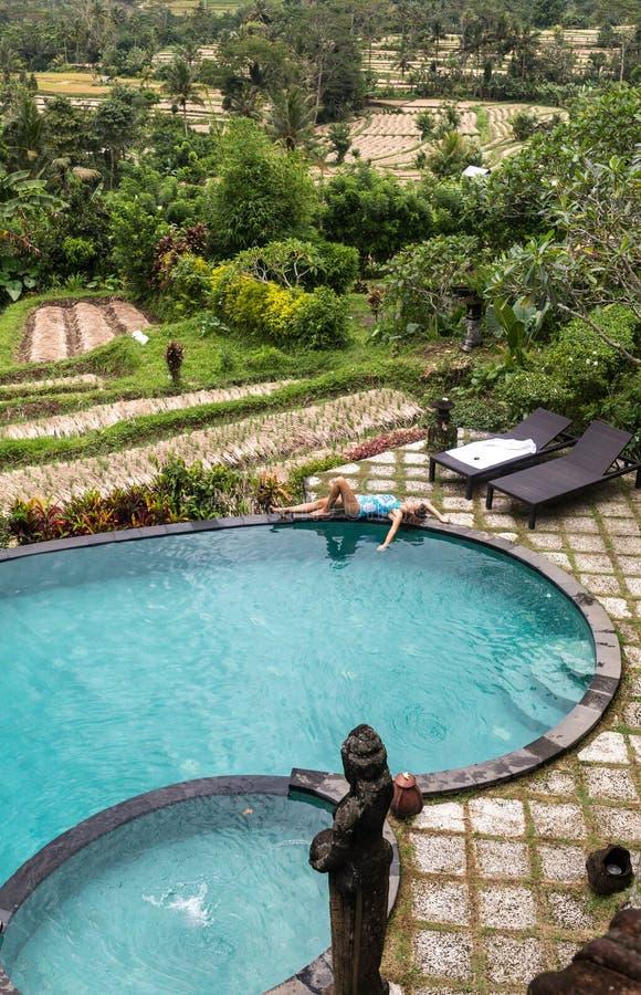 Muchacha en piscina del infinito hacia selva con palmtrees imagenes de archivo