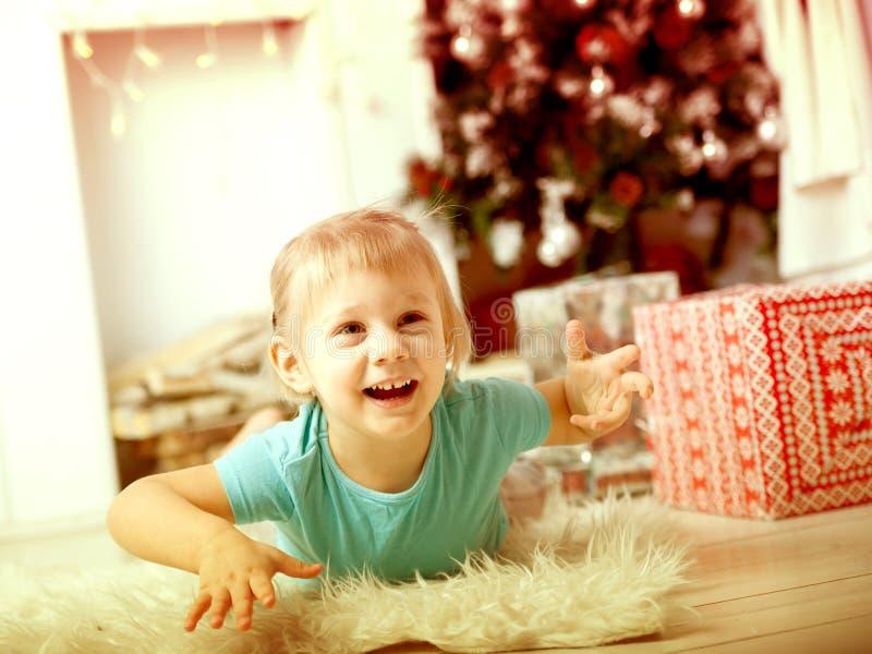 Muchacha en piso al lado de los regalos retro foto de archivo