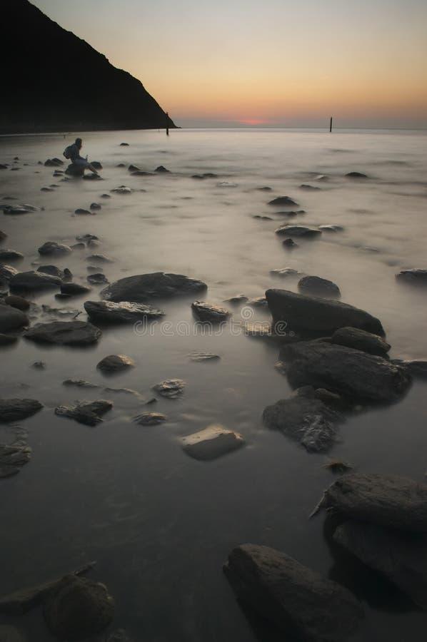 Muchacha en puesta del sol en rocas imagen de archivo libre de regalías