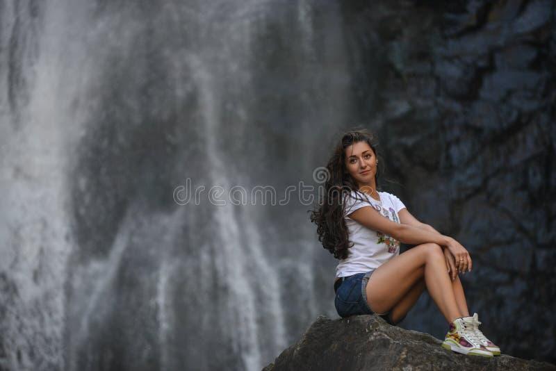 Muchacha en roca con el fondo de la cascada fotos de archivo libres de regalías