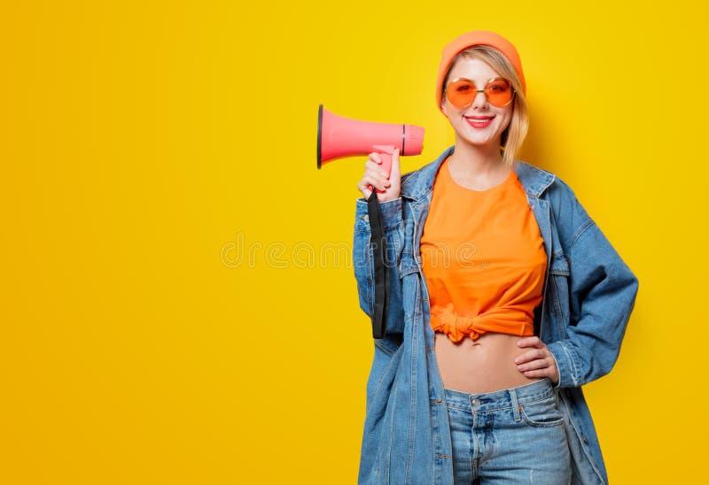 Muchacha en ropa de los vaqueros con el megáfono rosado imágenes de archivo libres de regalías