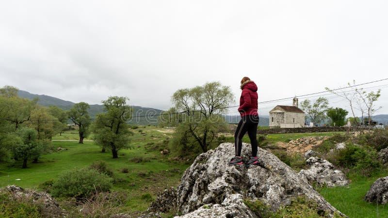 Muchacha en ropa del deporte y chaqueta roja del invierno en un pequeño pueblo de Montenegro con la pequeña capilla ortodoxa imágenes de archivo libres de regalías