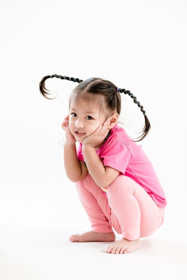 Muchacha en rosa con el peinado divertido que se sienta en el fondo blanco fotografía de archivo libre de regalías