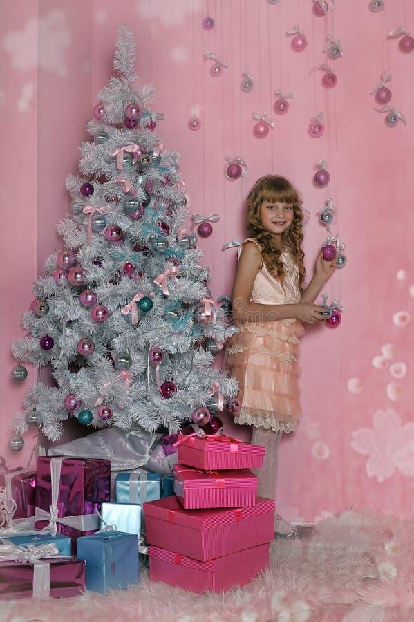 Muchacha en rosa en el árbol de navidad fotografía de archivo libre de regalías