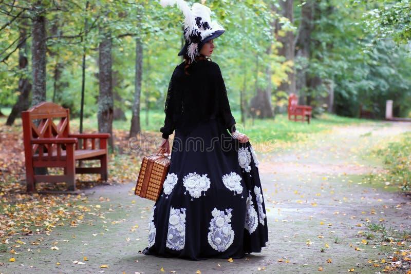 Muchacha en siglo XVIII retro del vestido con el valise en parque fotografía de archivo libre de regalías