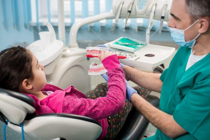 Muchacha en silla del dentista que educa sobre el diente-cepillado apropiado de su dentista pediátrico imagen de archivo