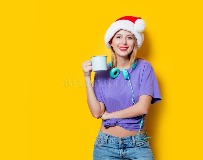 Muchacha en sombrero de la Navidad con la taza foto de archivo