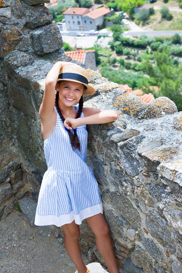 Muchacha en sombrero de paja cerca de la pared antigua en Eus, Francia fotografía de archivo