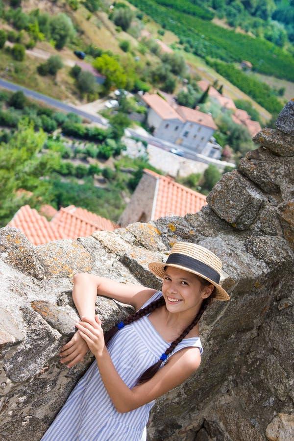 Muchacha en sombrero de paja cerca de la pared antigua en Eus, Francia imagen de archivo
