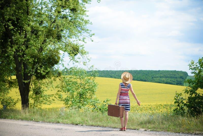 Muchacha en sombrero de paja con la maleta retra cerca del verano imágenes de archivo libres de regalías