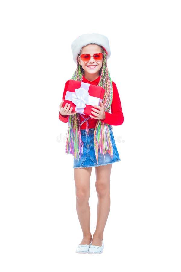Muchacha en sombrero del ` s de santa El retrato de la pequeña muchacha linda que lleva a cabo la caja de regalo de Navidad, pequ foto de archivo libre de regalías
