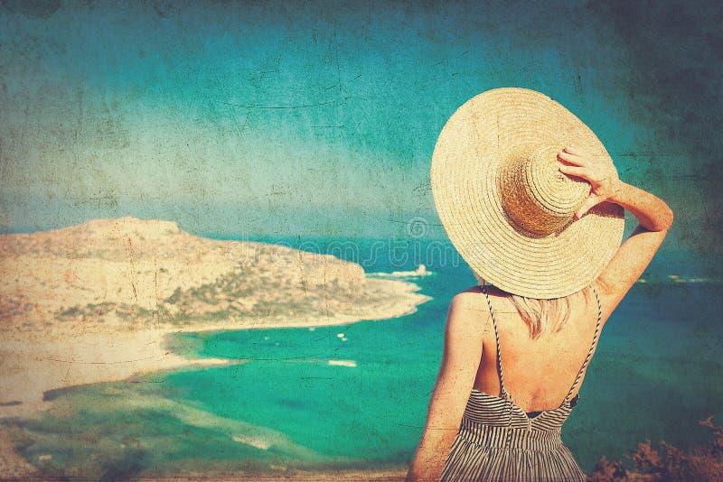 Muchacha en sombrero y vestido con la costa costa del mar foto de archivo