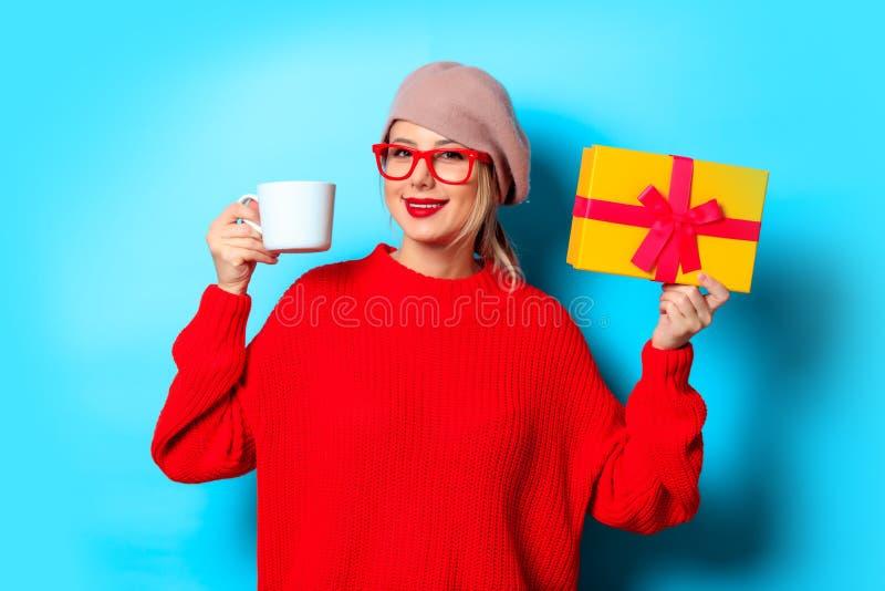 Muchacha en suéter rojo con la caja de regalo y la taza de café fotografía de archivo