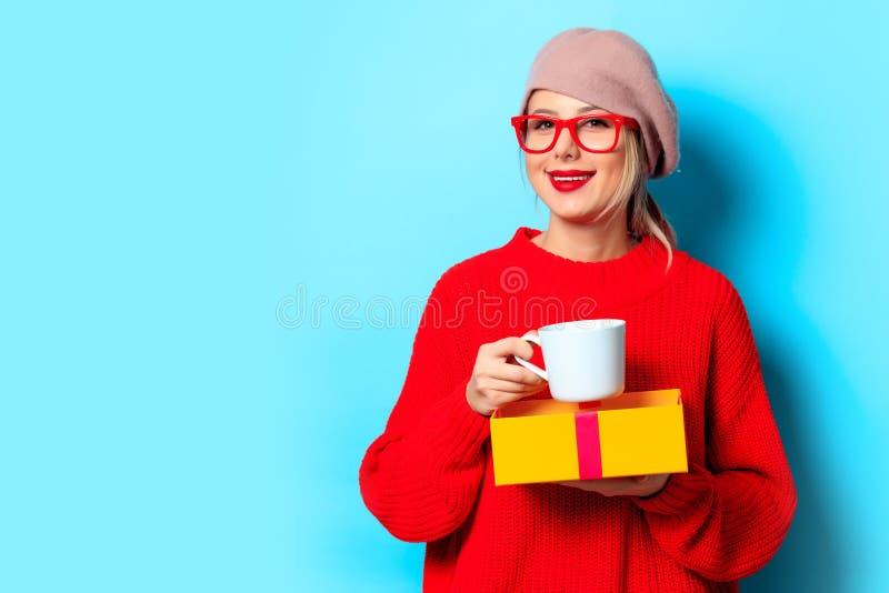 Muchacha en suéter rojo con la caja de regalo y la taza de café imagen de archivo libre de regalías