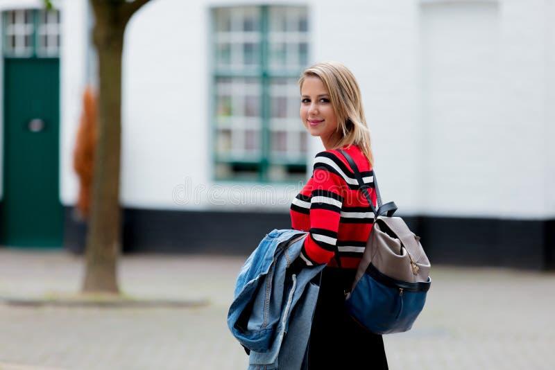 Muchacha en suéter y chaqueta en la calle de Brujas fotos de archivo