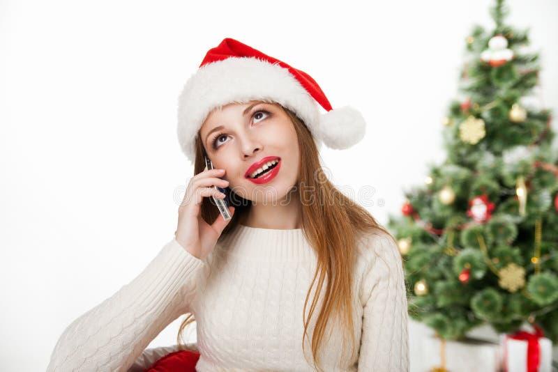 Muchacha en teléfono de la llamada del sombrero de santa por el árbol de navidad foto de archivo libre de regalías